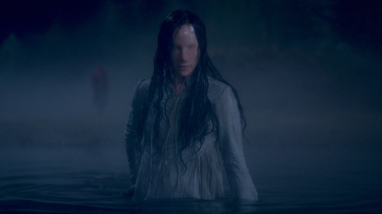 The Lady in The Lake in The Haunting of Bly Manor. A mysterious ghostly woman with no facial features, standing in the middle of a dark body of water. Her white dress and long black hair are soaked through, she moves towards the camera menacingly.
