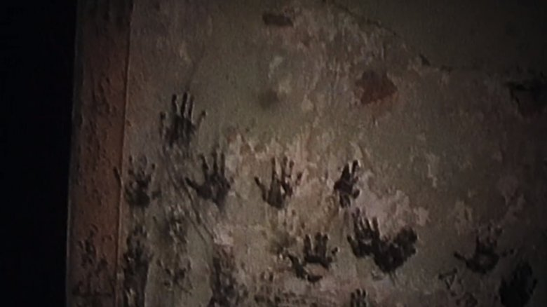 Child size handprints on a wall