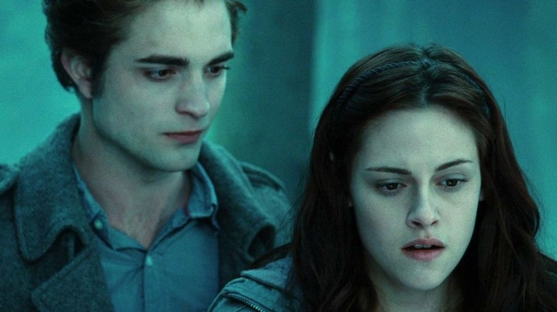 Edward and Bella stand in forest in Twilight