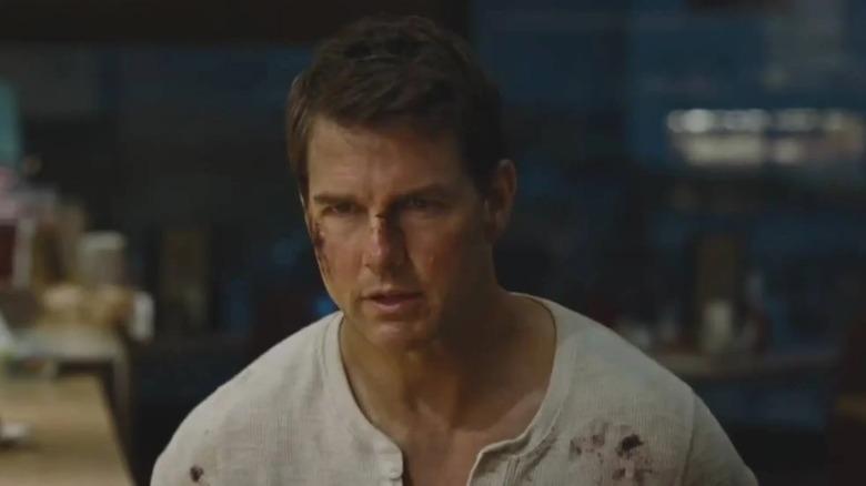 Tom Cruise wears a bloody shirt in Jack Reacher