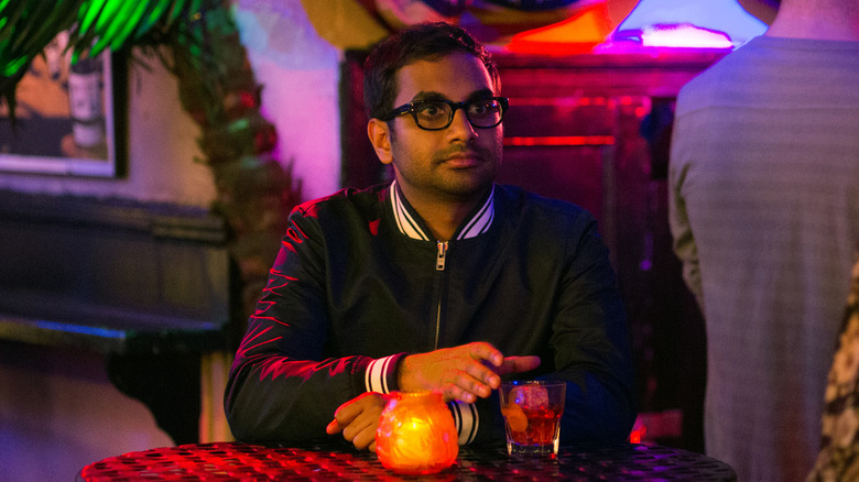 Aziz Ansari sitting at table