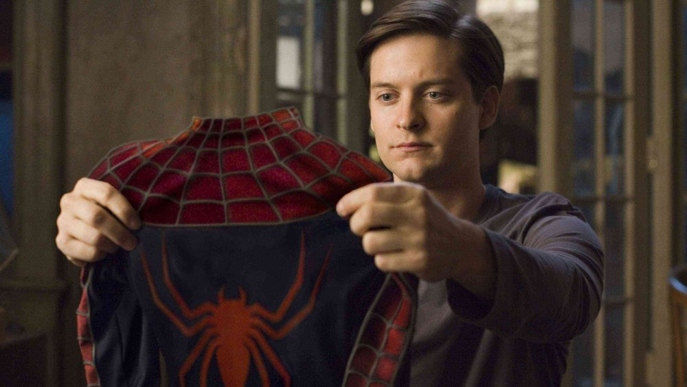 Tobey Maguire as Peter Parker inspecting his Spidey suit in Spider-Man