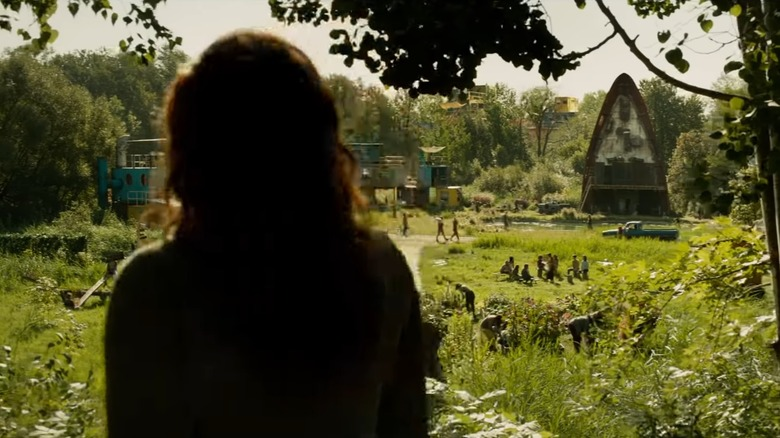 Jean Grey peers through trees at a strange island stronghold