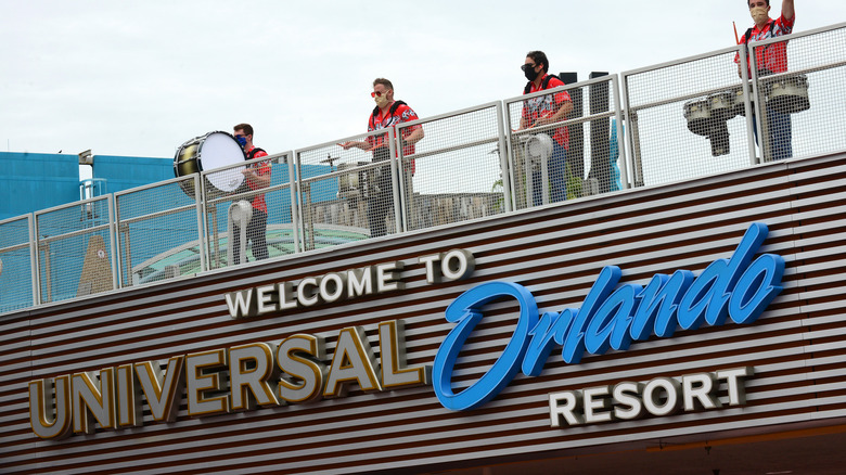 sign for Universal Orlando Resort; performers in masks