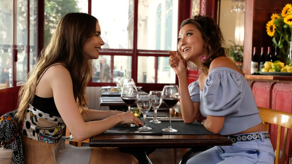 Lily Collins as Emily and Ashley Park as Mindy in Emily in Paris