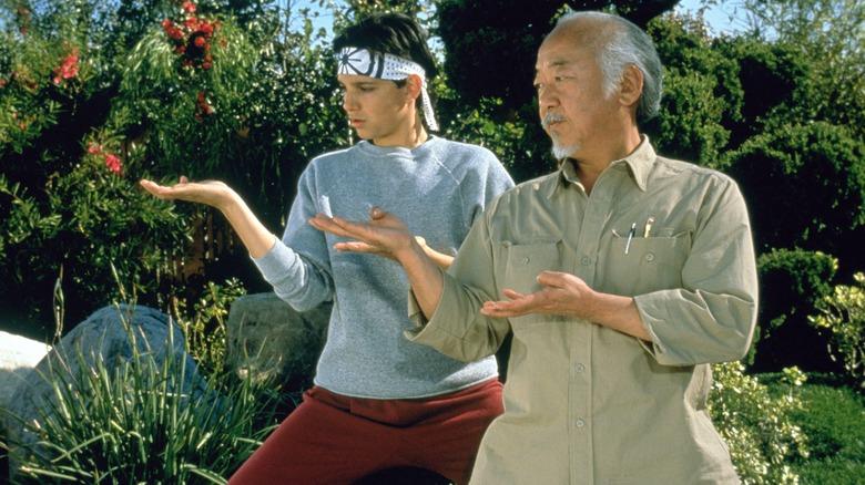 Daniel Larusso and Mr. Miyagi do karate in The Karate Kid