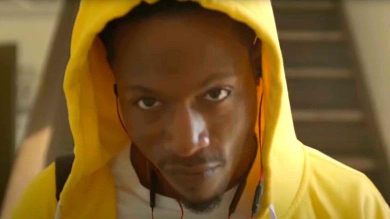 Joey Bada$$ in a hoodie looking at camera
