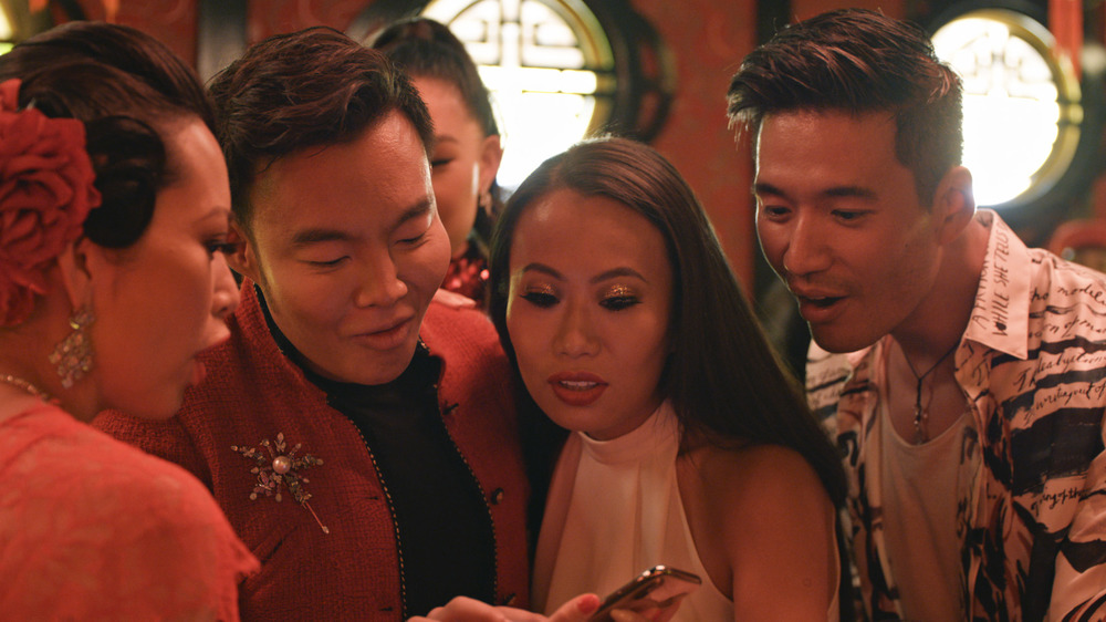 Bling Empire cast looking at mobile phone