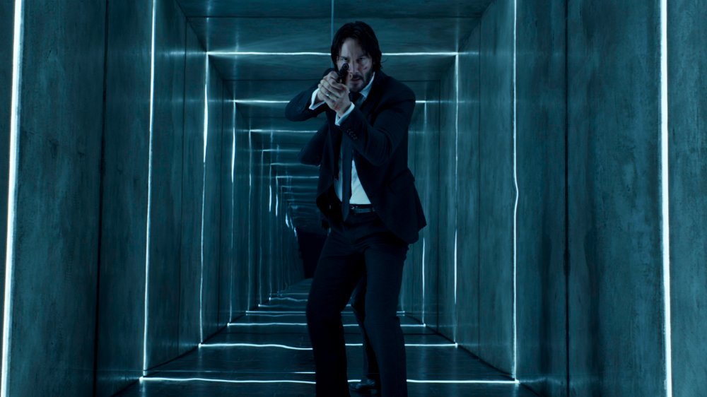 John Wick, pistol drawn, enters the Reflections of the Soul exhibit
