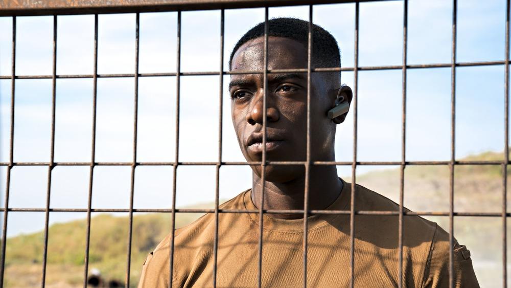 Damson Idris as Harp peers through a fence