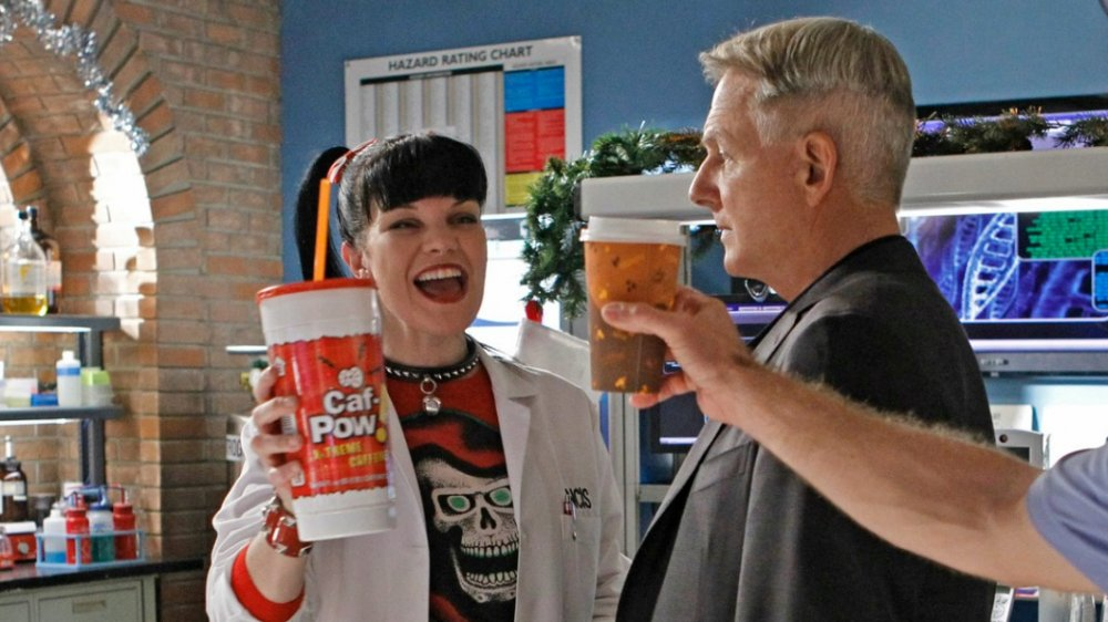 Pauley Perrette as Abby Sciuto gleefully holds a cup of Caf-Pow while Mark Harmon as Leroy Jethro Gibbs looks fed up in NCIS