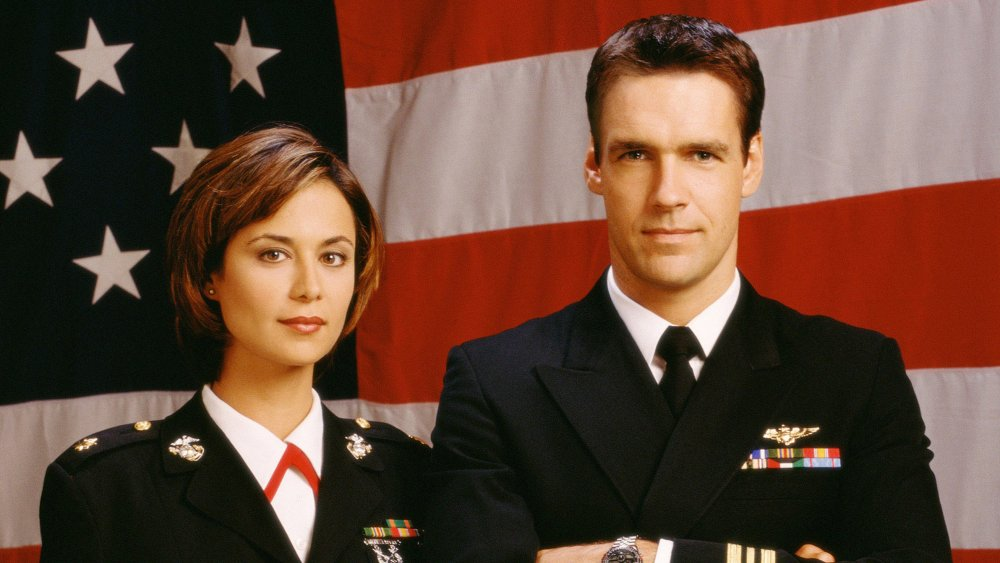 Catherine Bell as Sarah 'Mac' Mackenzie and David James Elliot as Harmon 'Harm' Rabb Jr. stand in front of the Stars and Stripes in uniform in JAG
