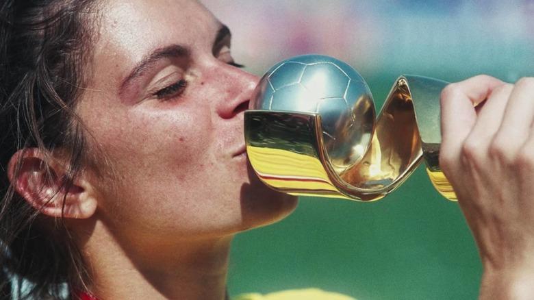 Soccer player kissing trophy