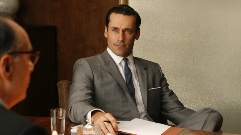 Jon Hamm as Don Draper sitting in a chair in Mad Men