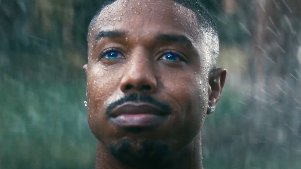 Michael B. Jordan with blue eyes getting sprayed by sprinklers