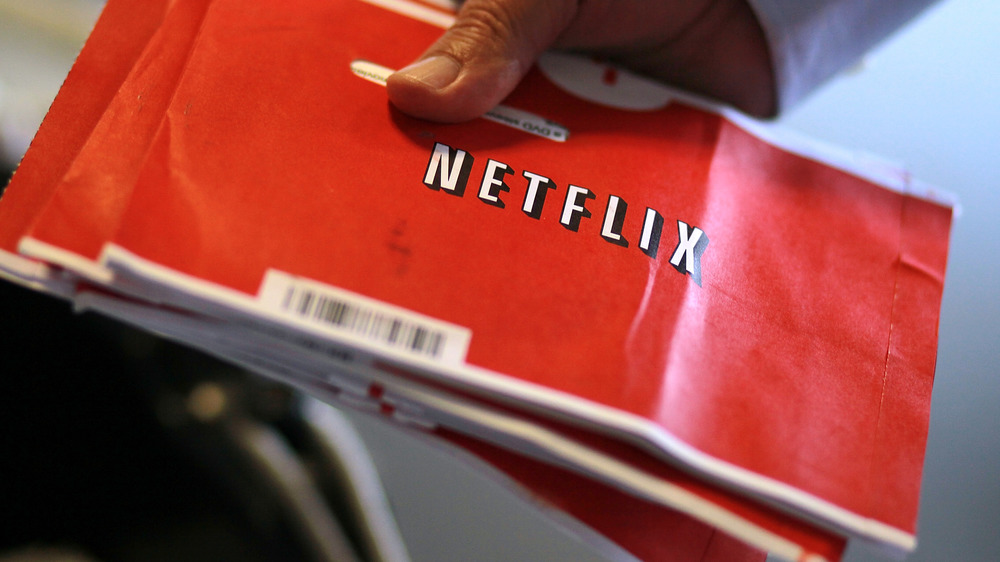 Man holding Netflix DVD envelopes