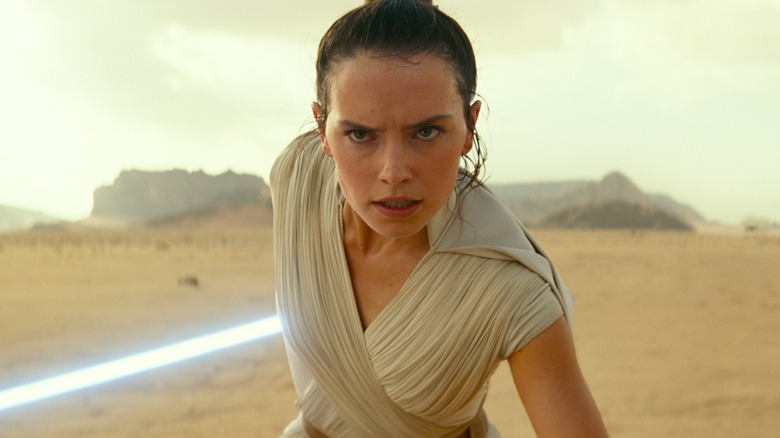 Daisy Ridley as Rey with lightsaber in The Rise of Skywalker
