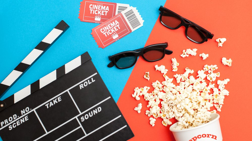 Movie tickets, popcorn, film slate, and 3D cinema glasses