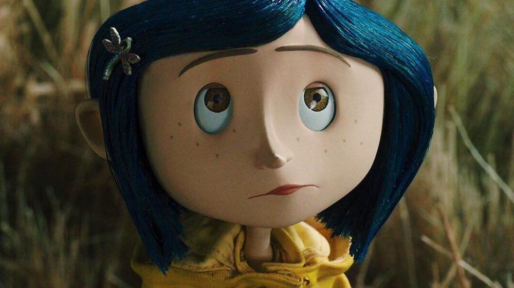 Coraline in yellow raincoat looking up at something in Coraline